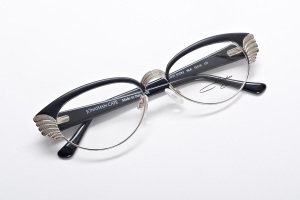 Folded view of black and silver retro inspired cat eye glasses with wings.